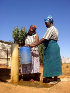 South african women using water pump